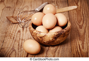 fresh brown eggs with egg whisk on wooden background
