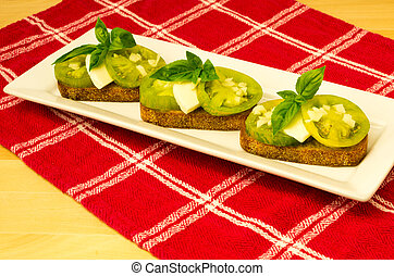 Fresh bruschetta with green heirloom tomatoes cheese and basil on red cloth