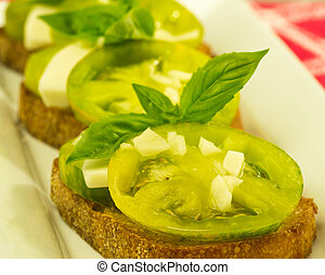 Fresh bruschetta with green heirloom tomatoes cheese and basil on white plate