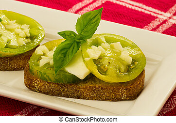 Fresh bruschetta with green heirloom tomatoes cheese and basil