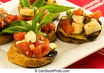 Fresh bruschetta with tomatoes cheese basil on white plate