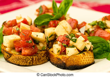 Fresh bruschetta with tomatoes mozzarella cheese and basil on toast on white plate