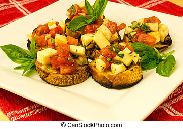 Fresh bruschetta with tomatoes mozzarella cheese and basil on white plate