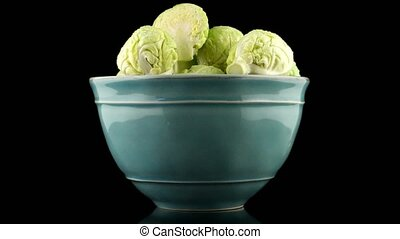 Fresh brussels sprouts on blue ceramic bowl isolated on black background.