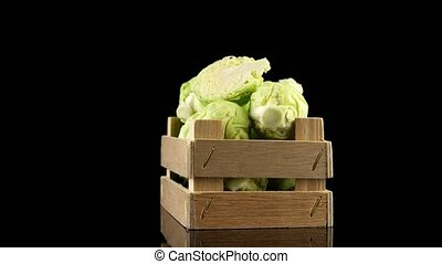 Fresh brussels sprouts on wooden box isolated on black background.
