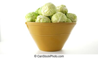Fresh brussels sprouts on green ceramic bowl isolated on...