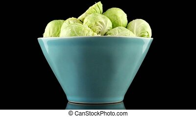 Fresh brussels sprouts on blue ceramic bowl isolated on...