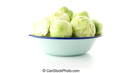 Fresh brussels sprouts on blue metal bowl isolated on white...