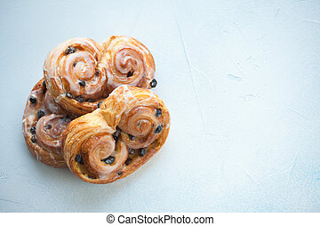 Fresh buns with raisins and icing on blue background. Top view with copy space