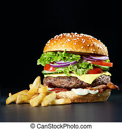 Fresh burger with french fries on dark background