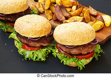 Fresh burgers with fried potatoes on wooden board. Side view.