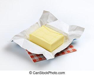 Fresh butter - Block of fresh butter resting on a wrapper