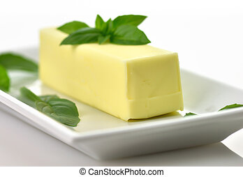 fresh butter - Fresh Butter stick on a white dish with basil...