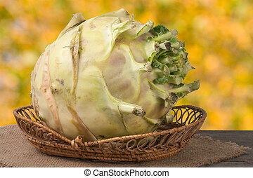 fresh cabbage kohlrabi in a wicker basket on dark wooden table with blurred background