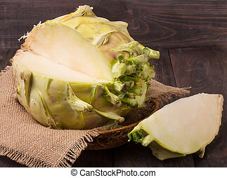 fresh cabbage kohlrabi in a wicker basket on dark wooden table with sackcloth