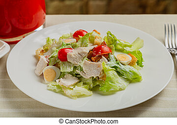 Fresh caesar salad in a white plate on the table.