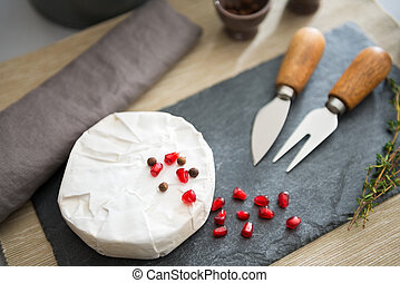 Fresh Camembert cheese on a slate with pomegranate seeds - A...