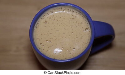 Fresh cappuccino with foam in a blue cup