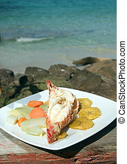 fresh Caribbean lobster tails cooked garlic and butter with local vegetables as photographed in Big Corn Island Nicaragua Central America