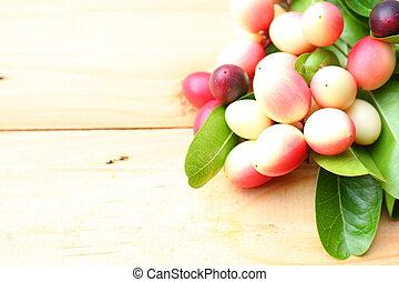 Fresh carissa carandas fruits on wooden background