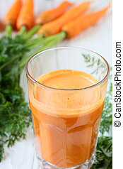 fresh carrot juice in a tall glass and carrots
