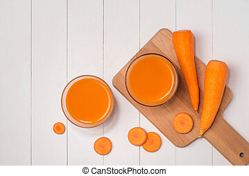 Fresh carrot juice in glass on wooden table.