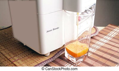 Fresh carrot juice pours of juicers in a glass on the table....