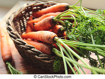 Fresh carrots in a wooden wicker on kitchen table