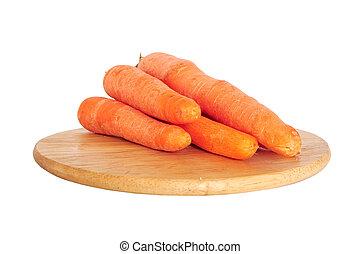 Fresh carrots on wooden board