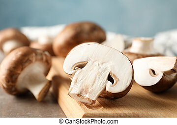 Fresh champignon mushrooms and wood board on grey background, close up