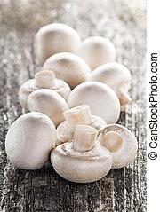 fresh champignon mushrooms close up on wooden table