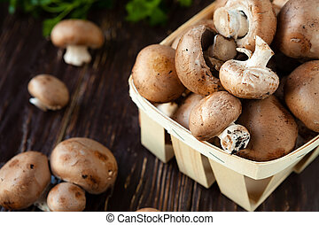 fresh champignons in a basket and greens