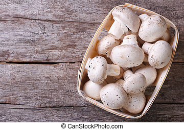Fresh champignons in a container on an old wooden table