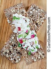 Fresh cheese salad with radish and herbs on crisp bread