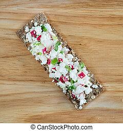 Fresh cheese salad with radish and herbs on crispbread