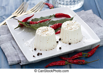 fresh cheese with pepper on white plate on blue wooden background