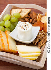 fresh cheese with pepper, toasts and grapes