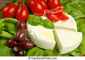 fresh cheese with salad, tomatoes and black olives