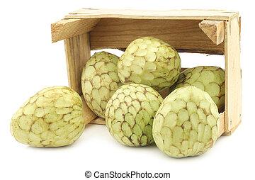 fresh cherimoya fruits (Annona cherimola) in a wooden crate