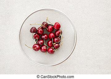 Fresh cherries in a round colander