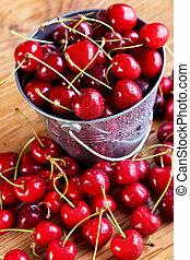 Fresh cherries in a small bucket - Fresh cherries on wooden...