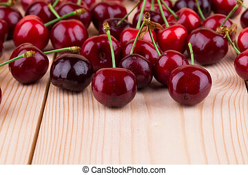 Fresh cherries on wooden table in the closeup.