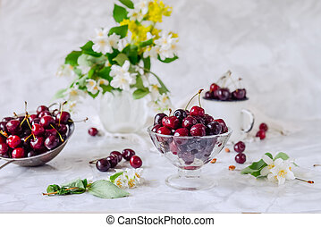 Fresh cherry fruit in glass vase, other dishes with berries and jar with jasmine and wildflowers on the light marble table. Soft selective focus. Summer countryside concept