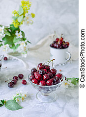 Fresh cherry fruit in glass vase, other dishes with berries and jar with jasmine and wildflowers on the light marble table. Soft selective focus. Summer country house concept
