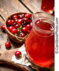 Fresh cherry juice .On wooden background.