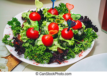 Fresh cherry tomatoes and salad in a white plate
