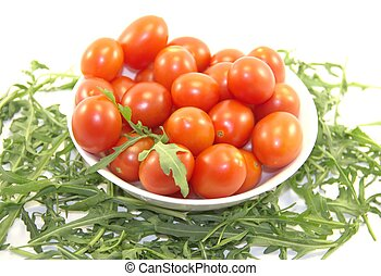 Fresh cherry tomatoes in a plate and rocket isolated on white background