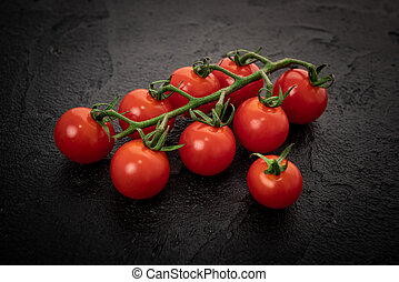 Fresh cherry tomatoes on a black background