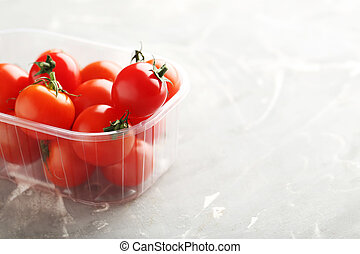 Fresh cherry tomatoes on a grey background