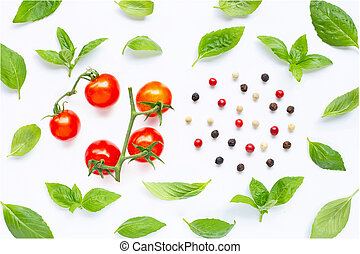 Fresh cherry tomatoes with basil leaves and different type of peppercorns on white
